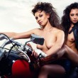 Stock Photo: Two sexy young woman sitting on a motorcycle