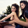 Stock Photo: Two sexy young woman sitting on a motorcycle outdoors