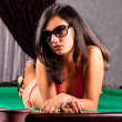 Seductive young girl in red bikini on a pool table — Stockfoto