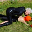 Stock Photo: Mistress in Black Latex Rubber Catsuit and Her Slave Girl