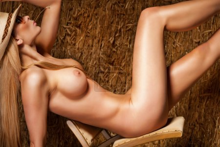 Beautiful, naked and sexy woman on hay background
